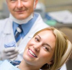 Woman smiling in the dental chair with her dentist behind her